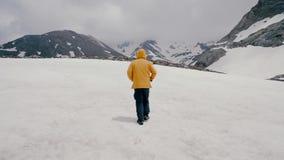 一件黄色外套的一个人走在积雪的领域的 股票录像