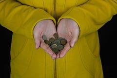 一件黄色外套的一个女孩在她的手上拿着一枚硬币在黑背景事务 免版税库存图片