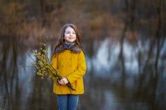 一件黄色外套的一个女孩在森林里在早期的春天有枝杈杨柳分支的  女孩furing的涨水或水位高 免版税库存图片