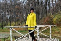 一件黄色外套的一名妇女在计数列夫・托尔斯泰庄园的桦树桥梁站立在Yasnaya Polyana 免版税库存图片