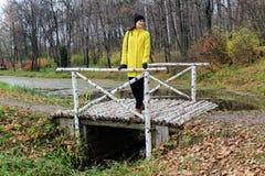 一件黄色外套的一名妇女在计数列夫・托尔斯泰庄园的桦树桥梁站立在Yasnaya Polyana 库存照片