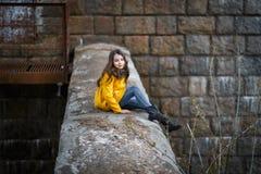 一件黄色外套的一女孩在日落的铁路铁桥梁下 库存照片