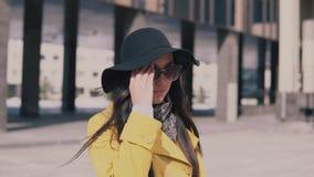 一件黄色外套的时髦的女孩有在帽子的长的黑发的步行沿着向下街道离开他的玻璃和神色  影视素材