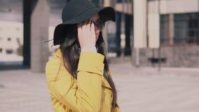 一件黄色外套的时髦的女孩有在帽子的长的黑发的步行沿着向下街道离开他的玻璃并且朝前看 影视素材