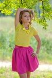 一件黄色女衬衫的年轻白肤金发的女孩有摆在明亮的太阳的光芒的一个夏天公园的一条明亮的桃红色裙子的 库存图片