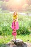 一件黄色女衬衫的年轻白肤金发的女孩有摆在明亮的太阳的光芒的一个夏天公园的一条明亮的桃红色裙子的 库存照片
