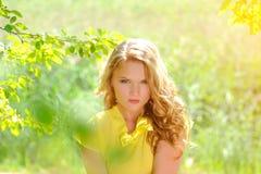 一件黄色女衬衫的年轻白肤金发的女孩有摆在明亮的太阳的光芒的一个夏天公园的一条明亮的桃红色裙子的 免版税库存照片