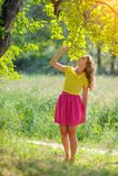 一件黄色女衬衫的年轻白肤金发的女孩有摆在明亮的太阳的光芒的一个夏天公园的一条明亮的桃红色裙子的 图库摄影