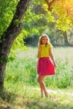 一件黄色女衬衫的年轻白肤金发的女孩有摆在明亮的太阳的光芒的一个夏天公园的一条明亮的桃红色裙子的 免版税库存图片
