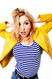 一件黄色明亮的夹克的惊奇的少女金发碧眼的女人看观察者 免版税库存图片