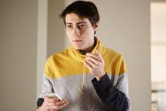 一件黄色毛线衣的一个英俊的年轻人在他的手和神色上周道地拿着一个电话对边 免版税库存照片