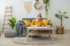 一件黄色毛线衣的少妇在家画 库存图片