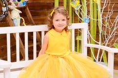 一件黄色礼服的女孩在长凳 免版税库存照片