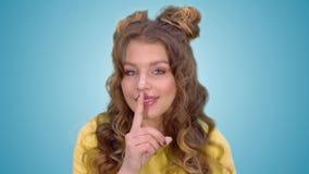一件黄色背心的美丽的少女投入手指到她的嘴唇并且显示姿态沈默和微笑的一会儿看 股票录像