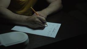 一件黄色T恤杉的一个人工作在黑暗的一张桌上 一个人用手写与铅笔在纸 r 影视素材