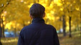 一件黑外套的年轻人在秋天公园 股票录像