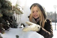 一件黑夹克的一个女孩接触冰柱 免版税库存照片