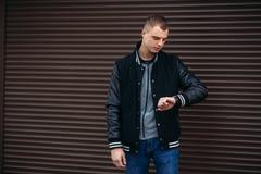 一件黑夹克的一个年轻人反对摆在和微笑对摄影师的黑暗的镶边墙壁背景  图库摄影