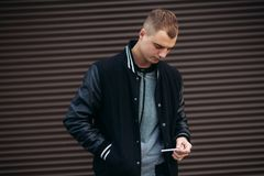 一件黑夹克的一个年轻人反对摆在和微笑对摄影师的黑暗的镶边墙壁背景  免版税图库摄影