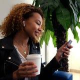 一件黑夹克的一个美丽的年轻非裔美国人的女孩有在她的耳朵微笑的airpairs的,举行每在她的白色玻璃 免版税库存图片