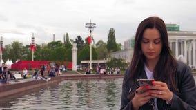 一件黑夹克的可爱的年轻女人使用智能手机 ?  影视素材