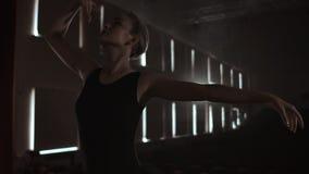 一件黑暗的礼服的优美的妇女芭蕾舞女演员在剧院的一个黑暗的阶段抽烟的在慢动作进行舞蹈移动 股票录像