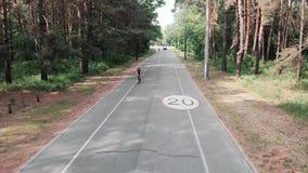 一件黑盔甲和桃红色运动服的被聚焦的年轻可爱的triathlete女孩在公园训练 Frontside跟随射击 Tr 股票录像