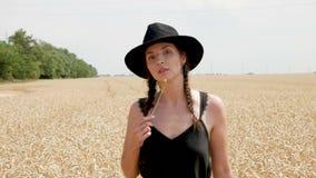一件黑礼服和帽子的妇女是在领域 股票录像