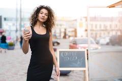 一件黑礼服的一个女孩步行沿着向下有一个电话的街道在她的手上 她想要快餐 库存图片