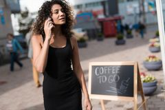 一件黑礼服的一个女孩步行沿着向下有一个电话的街道在她的手上 她想要快餐 图库摄影