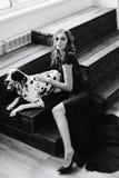 一件黑礼服的美丽的可爱的女孩有一条达尔马希亚狗的 库存照片