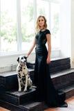 一件黑礼服的美丽的可爱的女孩有一条达尔马希亚狗的 免版税库存照片