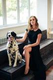 一件黑礼服的美丽的可爱的女孩有一条达尔马希亚狗的 免版税库存图片