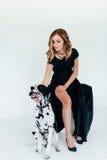 一件黑礼服的美丽的可爱的女孩有在白色背景的一条达尔马希亚狗的 免版税库存图片
