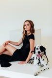 一件黑礼服的美丽的可爱的女孩有在白色背景的一条达尔马希亚狗的 库存照片