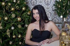 一件黑礼服的美女在圣诞树的背景 免版税图库摄影