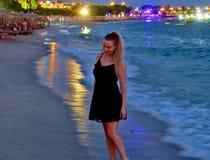 一件黑礼服的美女由海 免版税库存图片