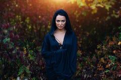 一件黑礼服的,有敞篷的一个斗篷一个女孩 它站立以秋天森林为背景 免版税库存照片