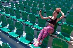 一件黑T恤杉的一个美丽的深色皮肤的女孩有的在她的耳朵的白色无线耳机单独坐fa的一把绿色椅子 免版税库存图片