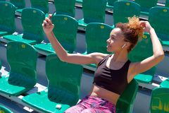 一件黑T恤杉的一个美丽的非裔美国人的女孩有的在她的耳朵的白色无线耳机单独坐f的一把绿色椅子 免版税库存照片