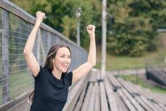 一件黑T恤杉的一年轻深色的妇女在体育场支持您喜爱的队的,喜欢举他的手并且微笑 免版税库存照片