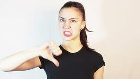 一件黑T恤杉的美丽的少女显示拇指下来并且厌恶地摇她的头 影视素材