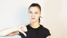 一件黑T恤杉的美丽的少女显示拇指下来并且厌恶地摇她的头 股票视频