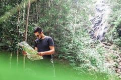 一件黑T恤杉的英俊的年轻时髦的mixed-race人有活跃区域的地图的在他的手上在密林,迁徙和 库存照片