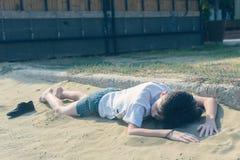 一件T恤杉和短裤的一个男孩与运动鞋在沙滩说谎 库存图片