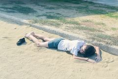 一件T恤杉和短裤的一个男孩与运动鞋在沙滩说谎 图库摄影
