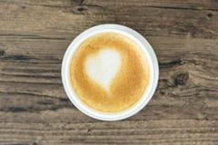 一份拿铁咖啡用艺术在棕色木桌上的心脏牛奶 库存照片