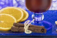 一份温暖的饮料的片段用桂香、桔子和姜蓝色玻璃表面上 库存图片