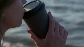 一份黑泳装饮用的咖啡的性感的女孩从在海滩的纸板玻璃 在日落的晚上在海旁边或 影视素材