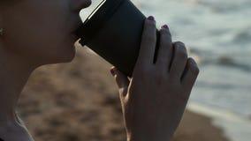 一份黑泳装饮用的咖啡的性感的女孩从在海滩的纸板玻璃 在日落的晚上在海旁边或 股票录像